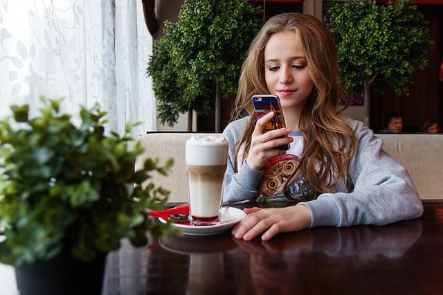 žena s mobilem v kavárně